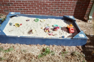 Can you find the toy tools buried in the sand?