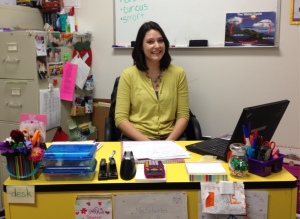 """The words """"curious"""" and """"smart"""" appear in bright marker on the board behind Beth Schetter."""